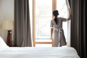 Female housekeeping opening window curtains