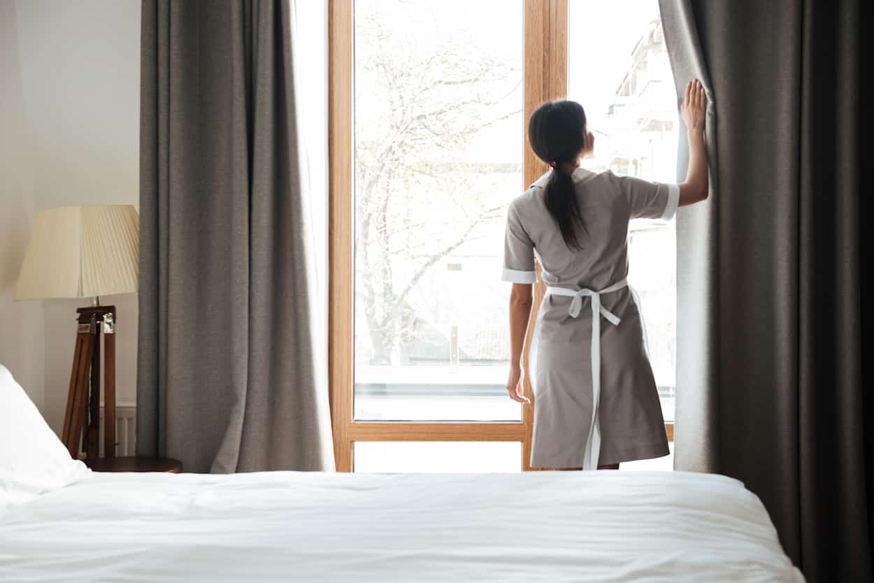 Female housekeeping opening window curtains