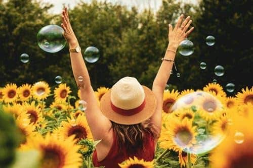 Woman enjoying a sunny day in a field of sunflowers
