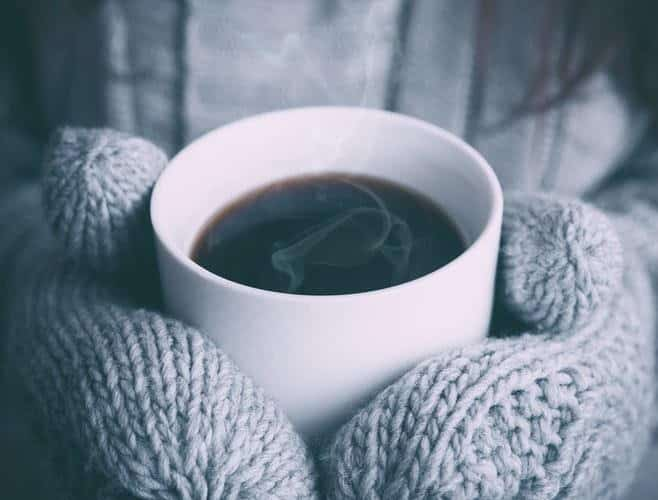 Cup of steaming black coffee held in woollen mits
