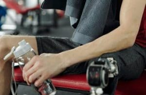 Man drinking from a water bottle in the gym