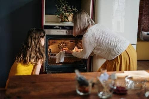 Mother and daughter using the oven in their kitchen