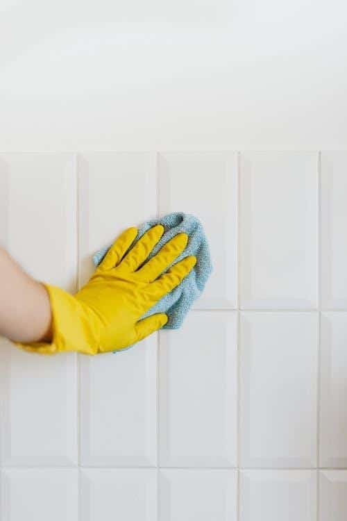 gloved hand cleaning tiles walls