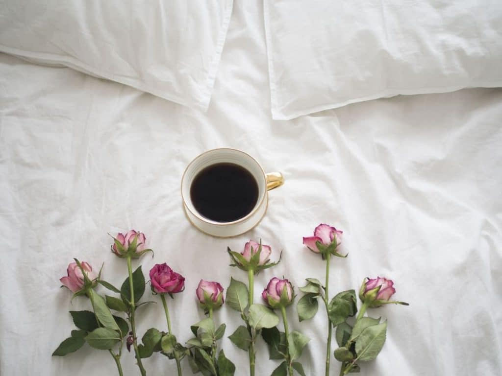 Lovely bed with cup of coffee and roses on it